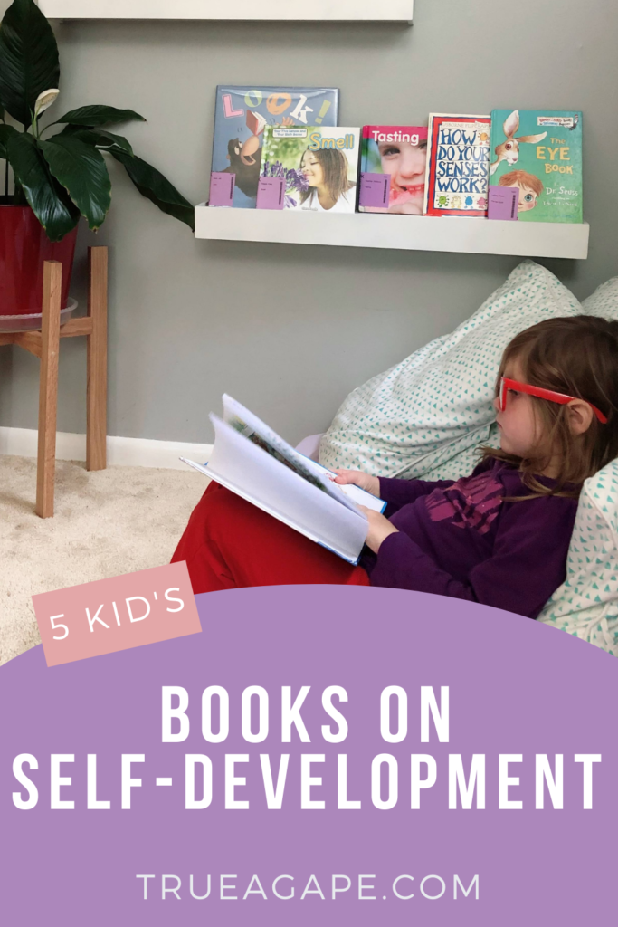 Child propped up on pillow with knees holding book up. Plant on stand and floating bookshelf with books in background.