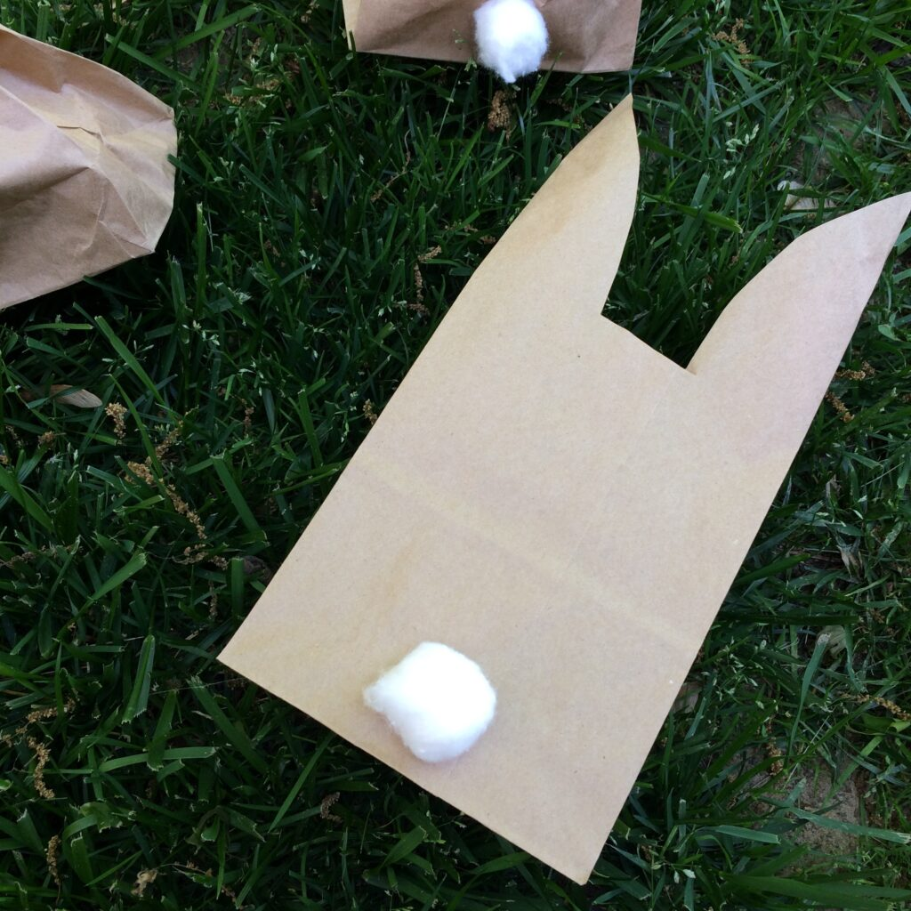 Brown paper lunch bag laying flat on ground with top cut out some to make rabbit ears.
